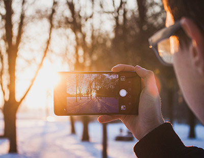 Young man in the snow taking photo of sunrise with mobile phone